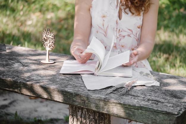 木製のテーブルで日記を書いたり、読んだりする女性。ロマンチックな思い出。ノートをめくって、公園の外でメモをとる。思い出、