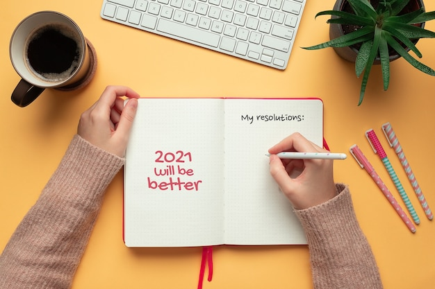 Woman writing resolutions in a 2021 new year notebook