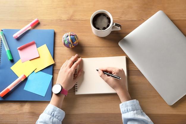 나무 테이블에 노트북에서 뭔가 쓰는 여자. 연구의 개념