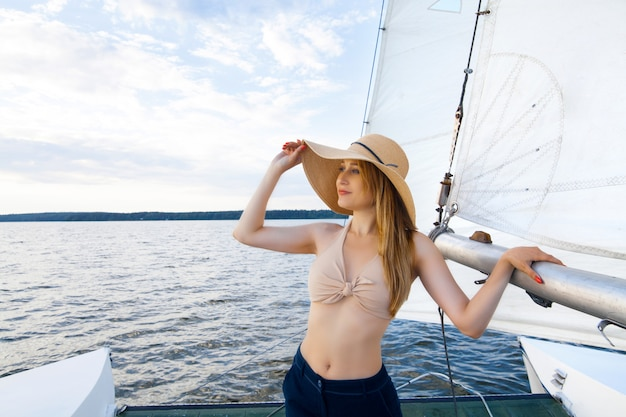 A woman on a yacht against the space of a sail and a blue sky. concept of sea recreation and travel.