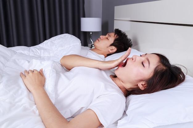 Женщина зевает и ее муж спит на кровати