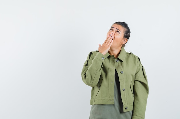 ジャケット、tシャツ、眠そうな顔を見上げながらあくびをする女性