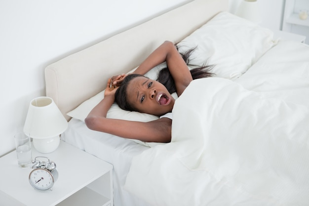 Woman yawning while waking up