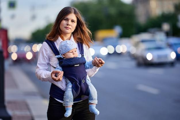 Женщина лет с младенцем в слинге гуляет возле пробок