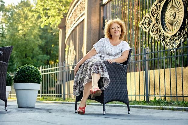 Женщина лет сидит в кресле возле кафе на тротуаре