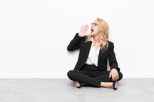 Женщина кричит громко и сердито, чтобы скопировать пространство сбоку, с рукой рядом со ртом
