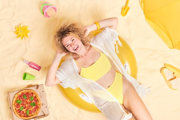 Woman in yellow bikini lies on inflatable swimring being in good mood has lazy day poses