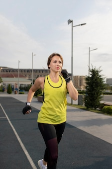 Woman in yellow and black sport outfits training, running in the street.