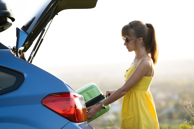 A woman in yellow dress taking green suitcase from car trunk. travel and vacations concept.