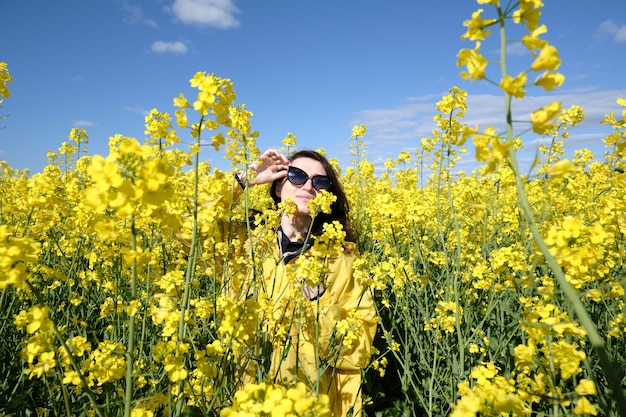 Woman and yellow flowers of rapeseed
