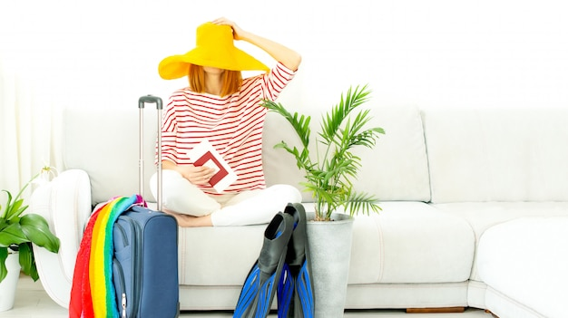 Woman in a yellow hat stays at home and plans a trip on vacation. suitcase and flippers for diving. closing borders and banning flights due to quarantine and covid-19.