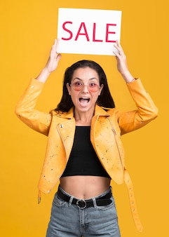 Woman in yellow jacket being surprised about the sales