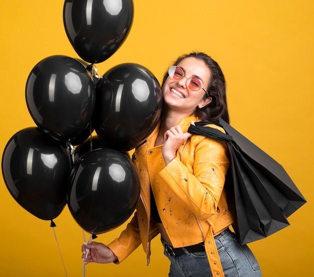 Woman in yellow jacket holding black friday balloons