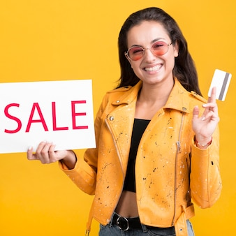 Woman in yellow jacket sale banner and credit card