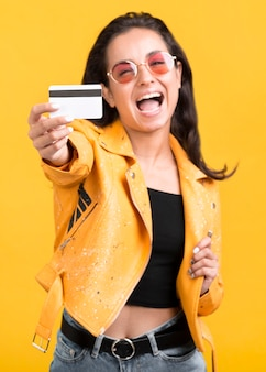 Woman in yellow jacket showing her shopping card