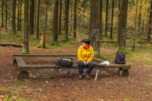 Woman in a yellow jacket, sitting on a bench in forest , having a break from hiking or trekking
