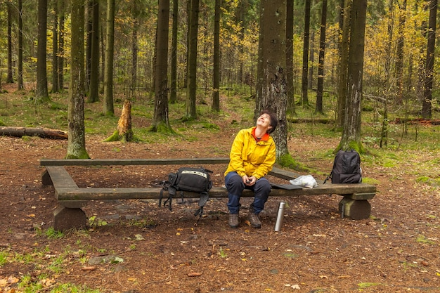 Woman in a yellow jacket, sitting on a bench, looking up and laughing in forest
