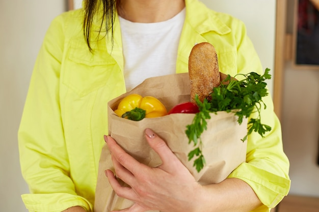 Woman in yellow jacket, standing with shopping paper bag full of fresh fruits and vegetables at home