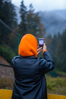 Woman in yellow raincoat hiker in autumn mountains copy space