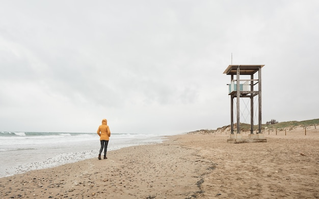 Woman in yellow raincoat looking at the sea. walk along the beach on a bad weather day.