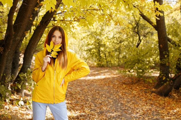 A woman in a yellow raincoat with an autumn leaf against the background of the autumn forest on a walk. autumn concept