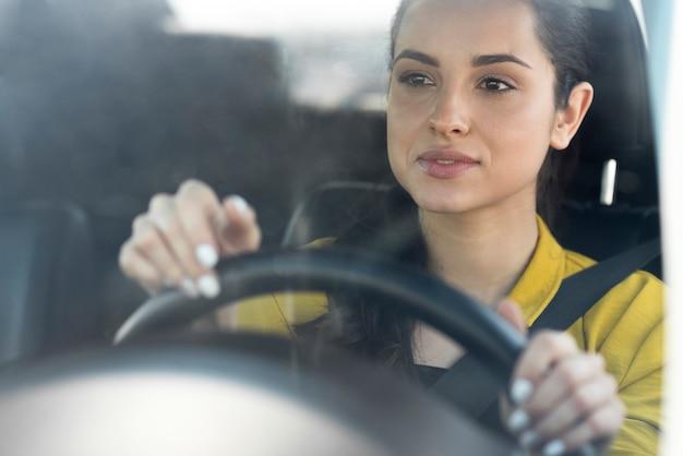 Woman in yellow shirt drives