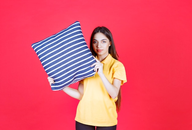 Woman in yellow shirt holding a blue pillow with white stripes.