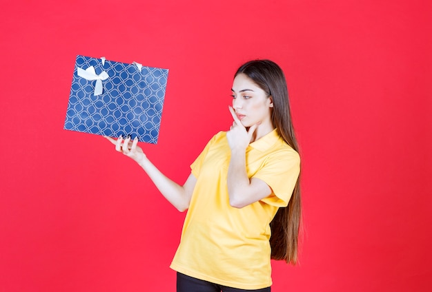 Woman in yellow shirt holding a blue shopping bag and looks confused and thoughtful.