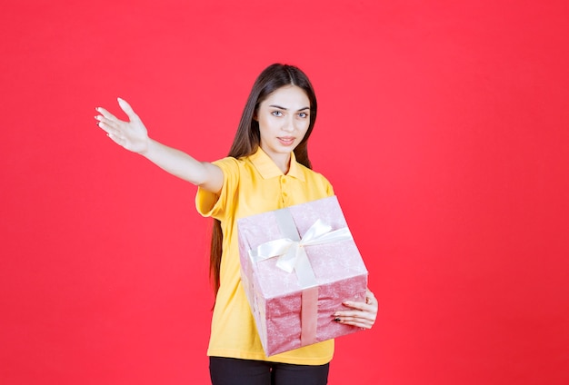Woman in yellow shirt holding a pink gift box and inviting someone to approach and take it.