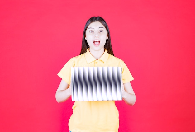 Woman in yellow shirt holding silver gift box and looks excited