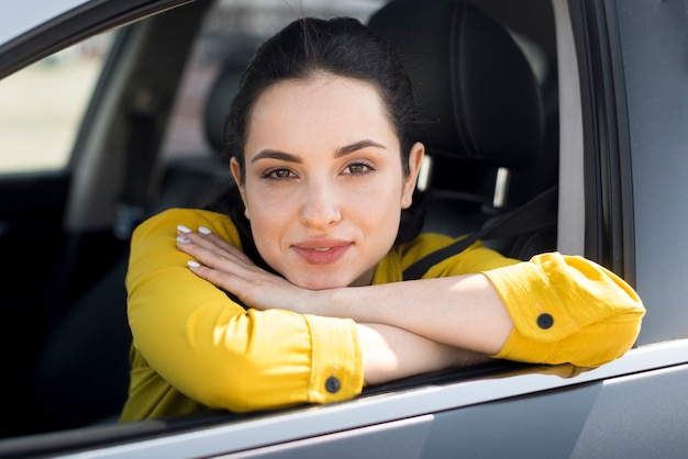 Woman in yellow shirt leaning on the window
