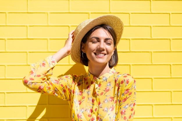 Woman in yellow summer dress and hat on yellow brick wall calm and positive, enjoys sunny summer days
