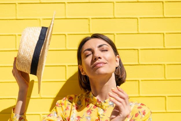 Donna in abito estivo giallo e cappello sul muro di mattoni gialli calma e positiva, gode di soleggiate giornate estive