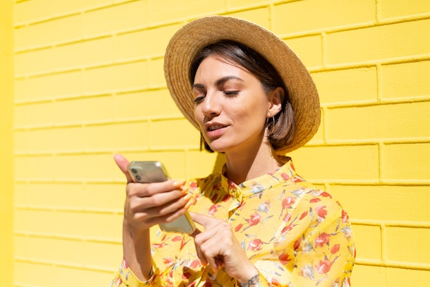 Woman in yellow summer dress and hat on yellow brick wall calm and positive holding mobile phone