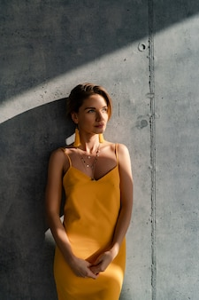 Woman in yellow summer dress with short hairstyle in interior room concrete wall posing
