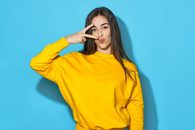 Woman in a yellow sweater on a blue background