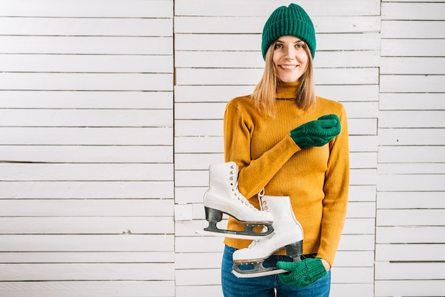 Woman in yellow sweater holding skates