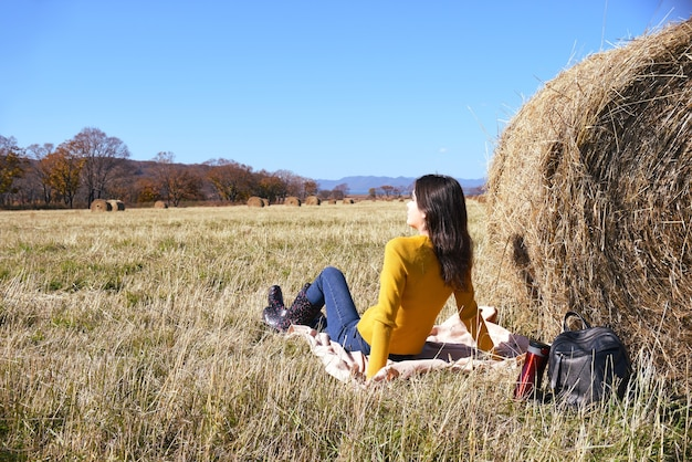 Woman in yellow sweater and rubber boots sitting on plaid next to backpack and thermos with tea