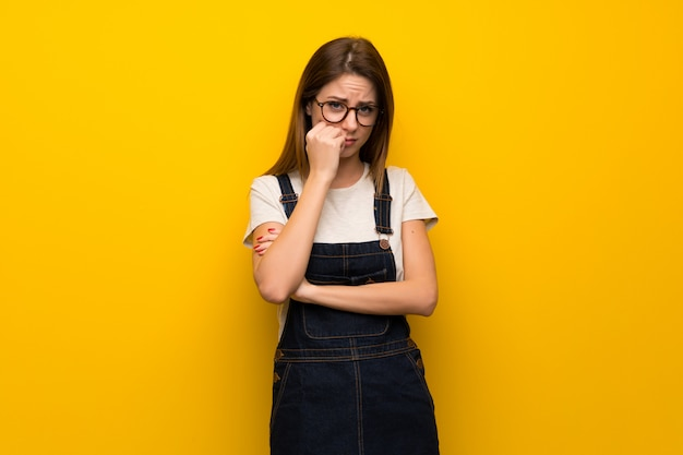 Woman over yellow wall having doubts