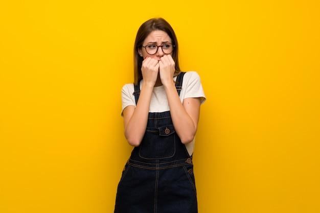 Woman over yellow wall nervous and scared putting hands to mouth