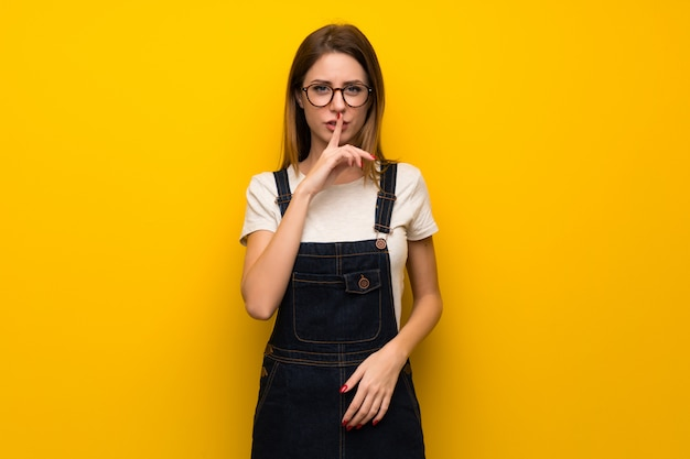 Woman over yellow wall showing a sign of silence gesture putting finger in mouth