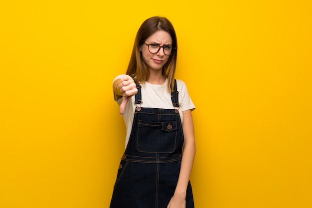 Woman over yellow wall showing thumb dowg with negative expression