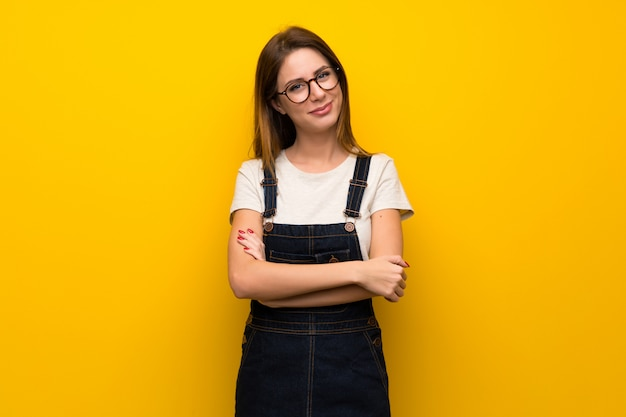 Woman over yellow wall smiling