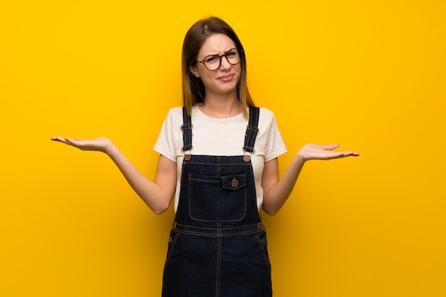 Woman over yellow wall unhappy because not understand something