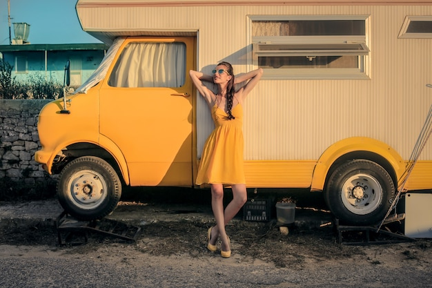 Woman in yellow with a yellow caravan