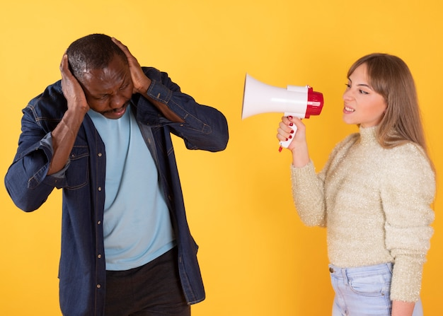 A woman yells at a man with an angry microphone, and a man covers his ears,