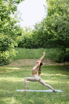 Woman in yoga asana park on green summer background