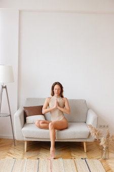 Woman yoga in beige bodysuit sits in asana on the sofa at home