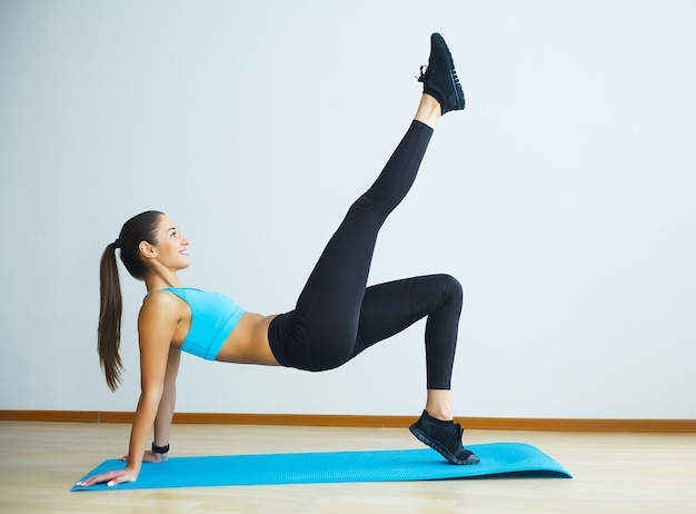 Woman in yoga class making upward-facing dog pose.