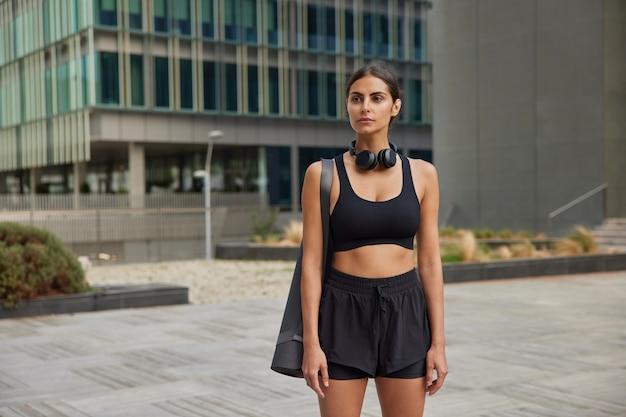 스트레칭 운동을 담당하는 여성 요가 강사는 스포츠 의상을 입고 균형을 유지하며 도시 건물 근처에서 필라테스 또는 에어로빅 개인 레슨을 제공합니다